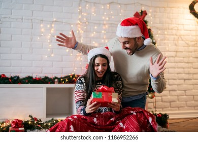 Presents time ! Young happy couple sharing new years presents while sitting on floor covered with blanket. Colorful christmas decoration in background.