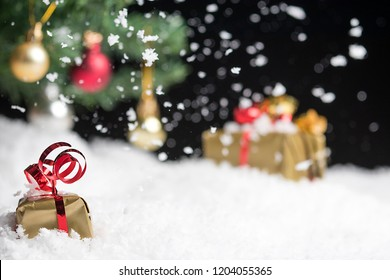 Presents wrapped in a colorful paper lie on the fake snow under the Christmas tree and the snow falls on them