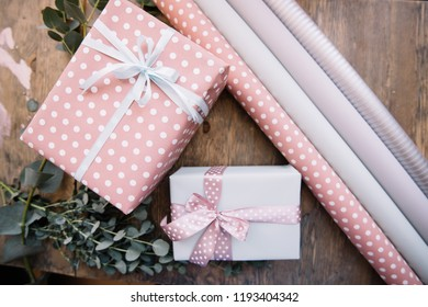 Presents wrapped in pink festive wrapping paper on the wooden rustic table background, top view, flat lay