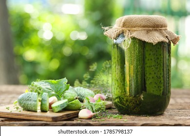 Preservations, conservation. Salted, pickled cucumbers in a jar on an old wooden table in the garden. Summer, sunny day. Cucumbers, herbs, dill, garlic. Rustic. Background image, copy space,horizontal