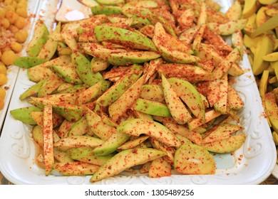 Preserve mango fruit spicy, sprinkle with sugar, chili powder and salt