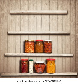 Preserved carrots, tomatoes, garlic, chilli, beans on shelf near a brown wooden wall
