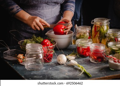 Preserved red bell peppers process fermented in glass jars kitchen table hand vegetarian canning food concept