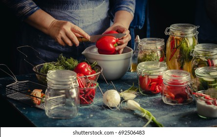 Preserved red bell peppers process fermented in glass jars kitchen table hand vegetarian canning food concept toned image
