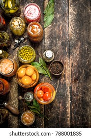 Preserved vegetables in glass jars with seamer. On a wooden background.