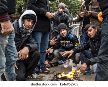 PRESEVO, SERBIA  - OCTOBER 24, 2015: Crowd of refugees waiting in from of a fire on a winter cold morning to register & enter Serbia at border with Macedonia on Balkans Route, during Refugee Crisis
