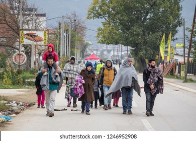 PRESEVO, SERBIA - OCTOBER 24, 2015: Family in front of a crowd of refugees on their way to register and enter Serbia at the border with Macedonia on Balkans Route, during  Refugee Crisis
