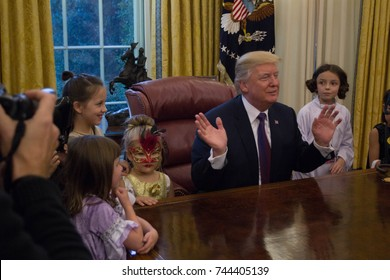 President Donald Trump poses for pictures with the children of White House journalists in the Oval Office, Friday, October 27, 2017.