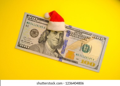 President Franklin in a red Santa Claus hat on a 100 US dollar bill on a bright yellow background. The concept of the cost of Christmas holidays, debt, profits or discounts for the new year.