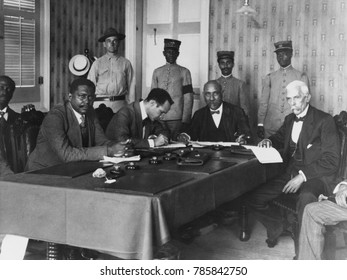President Philippe Sudre Dartiguenave, seated, 2nd from left, with cabinet ministers, Nov. 1915. In the left background, stands his bodyguard, US Marine Sergeant H.E. Miller. Dartiguenave was from Hai