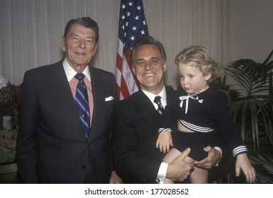 President Ronald Reagan and an admirer holding a child