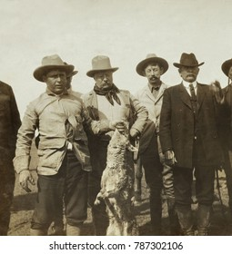President Theodore Roosevelt and his hunting companions near Frederick, Oklahoma, April 8-13, 1905. John R. Abernathy is holding a live coyote by the jaw. L-R: Abernathy, Roosevelt, Lee Bivins, S. Bur