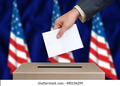 Presidential election in United States of America. The hand of man putting his vote in the ballot box. American flags on background.