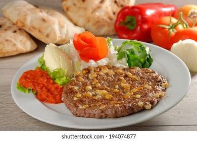 Presliced traditional burger patty called pljeskavica, served with pita bread with some cream cheese Kajmak. Balkan food