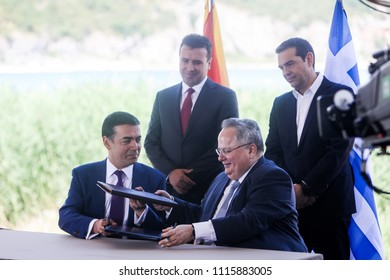 Prespes - Greece, June 17, 2018:Greek Foreign Minister N. Kotzias (down R) and his Macedonian counterpart N. Dimitrov (down L) sign a preliminary accord as A. Tsipras (R) and Z. Zaev (L) stand behind