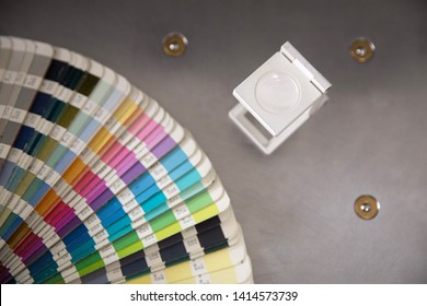Press color management. Cmyk stripe loupe and color palette on the guillotine cutter background.