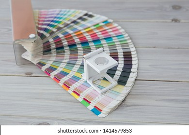 Press color management. Cmyk stripe loupe and color palette on the wooden background.