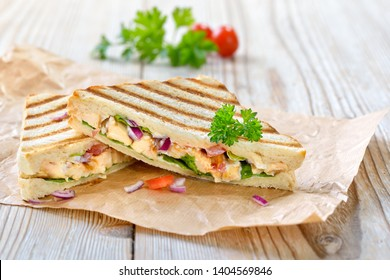 Pressed hot sandwich with grilled chicken breast fillet, tomatoes, onions and lettuce