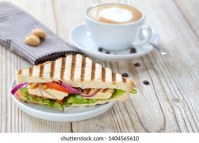 Pressed panini with grilled chicken breast fillet, tomatoes, onions and lettuce, served with a cappuccino