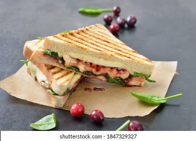 Pressed toast with grilled chicken breast, fresh spinach leaves, cranberry sauce and cheese served hot from the contact grill