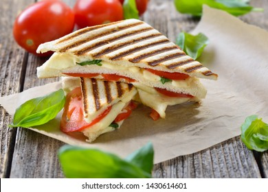 Pressed and toasted panini caprese with tomato, mozzarella and basil, served on sandwich paper on a wooden table