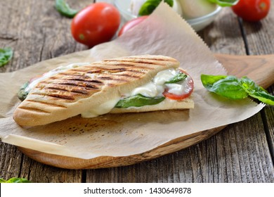 Pressed and toasted panini caprese with tomato, melted mozzarella and basil, served on sandwich paper on a wooden table