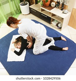 Pressing on girl back during yumeiho massage. This oriental therapy is a complex set of manual procedures and physical exercises. Above view