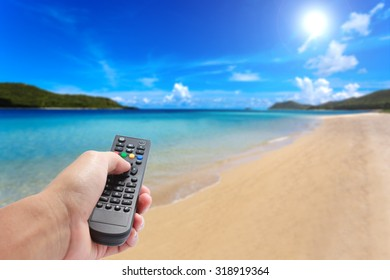 Pressing remote control to vacation and relax time on the beach