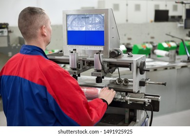 Pressman working on flexo plate mounting machine in printing factory. Flexographic printing machine is in the background. Printer is mounting flexographic printing plates on machine in press room.