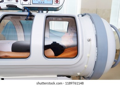 A pressure chamber with a girl lying inside.