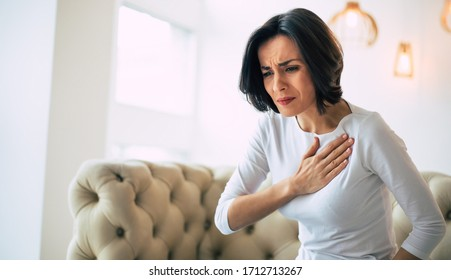 Pressure in the chest. Close-up photo of a stressed woman who is suffering from a chest pain and touching her heart area.
