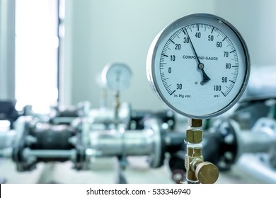 pressure compound gauge psi meter in pipe and valves of water system industrial focus left closeup white light defocus blur background