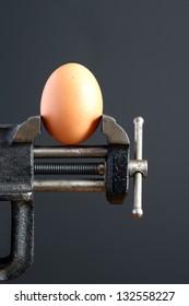 Pressure concept. Hen's egg pressured in a bench vice on dark background