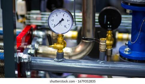 pressure gauge psi meter in pipe and valves of water system industrial focus left closeup white light defocus blur background.