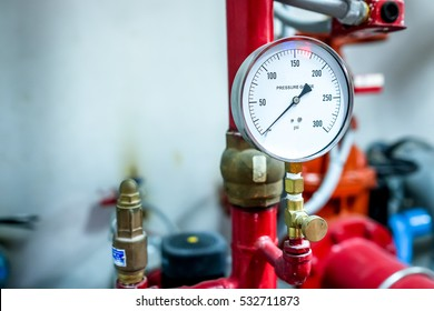 pressure gauge psi meter in pipe and valves of fire emergency system industry focus closeup left blank space red background