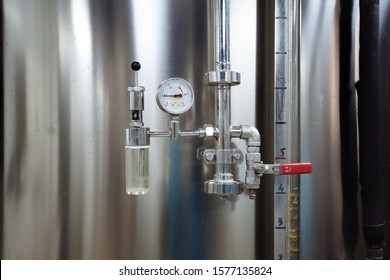 Pressure gauge and valve connected with steel tank in craft brewery.