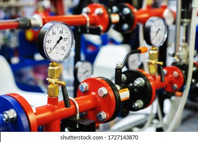 Pressure sensors in the urban heating system. Hot water pipes in an industrial boiler room. Mechanical barometer with arrow to control equipment parameters