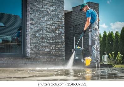 Druckreinigung vor dem Haus. Kaukasische Männer in seinen 30er Jahren waschen Betonsteine Fahrrad im sonnigen Sommertag. Reinigung rund um das Hauskonzept.