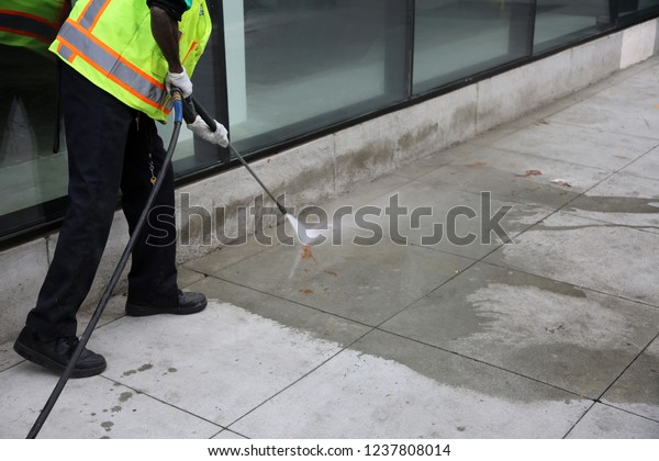 Pressure Washing. An unidentifiable city employee power washes blood or ketchup off a city sidewalk in downtown Los Angeles California.