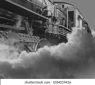 Pressurized steam forms a cloud next to a moving oil fired locomotive