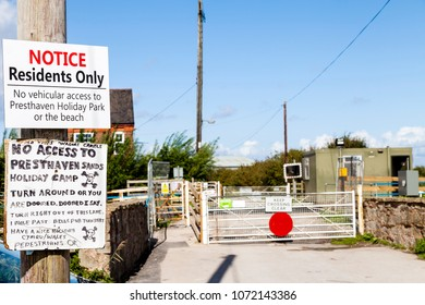 Prestatyn, North Wales- 8th September, 2017: Amusing notice attached to wooden post ahead of a railway crossing addressed to residents at Presthaven Sands holiday camp. No Access To Presthaven Sands
