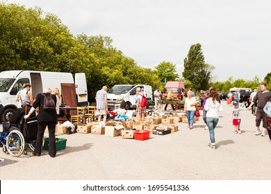 Prestatyn, North Wales UK - May 18 2014: Many people of all ages shopping at car boot sale lots of secondhanded and new goods in boxes on the tarmac tourists browse for a bargain.