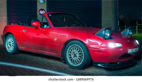 Preston, England, 27/02/2020 Preston detail garage car meet in the evening mazda mx5 na miata in red with BBS aftermarket wheels pop up headlights convertible sports car HDR image light painted