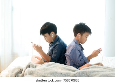 Preteen Asian Thai boy using a smartphone to play game on a white bed without care the surrounding.