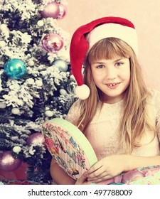 preteen blond girl in santa hat open present box on the christmas tree background close up photo