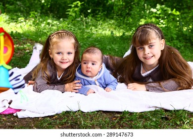 preteen blond little sister and baby boy brother lay on the summer park grass