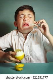preteen boy bite sore lemon make grimace