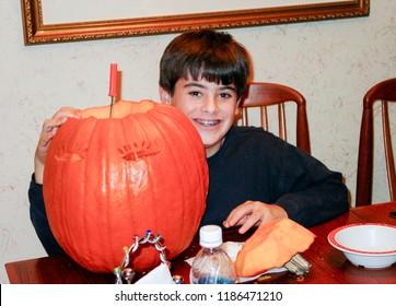 Preteen boy carving a pumpkin for Halloween