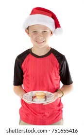 Pre-teen boy in christmas hat and a mince pie
