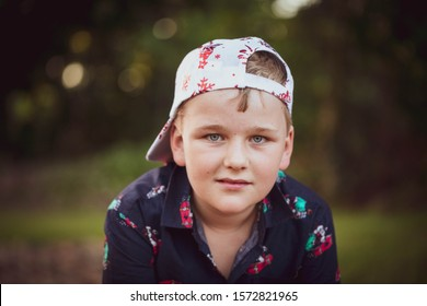 Pre-teen boy in Christmas outfit sitting in a relaxed style with hat backwards
